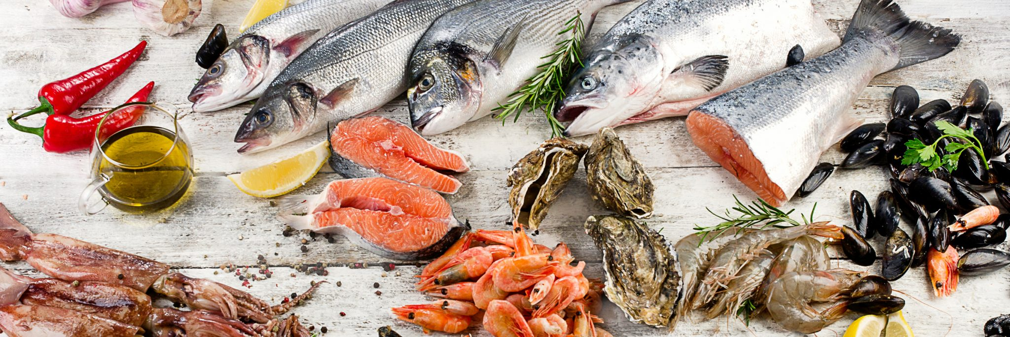 Fresh fish and other seafood on wooden background. Top view